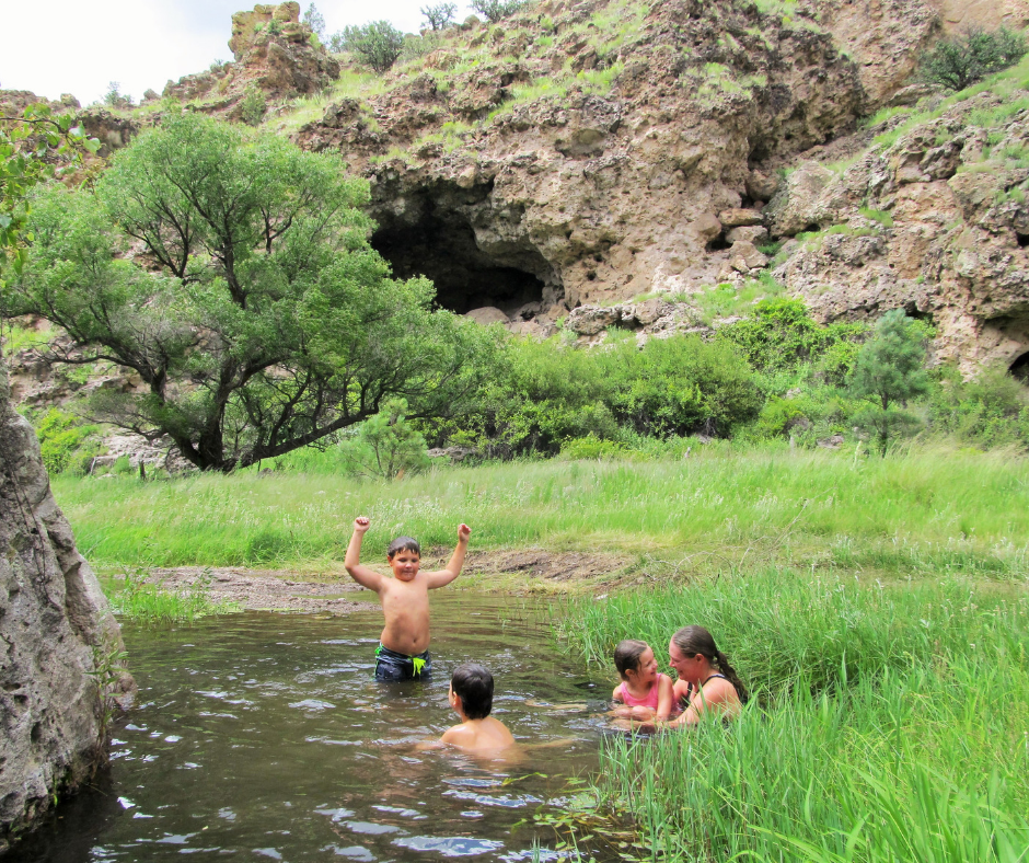 A family swimming in the creek at Geronimo Trail Guest Ranch.