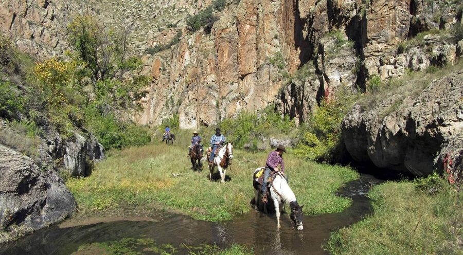 Riders crossing a stream in a canyon