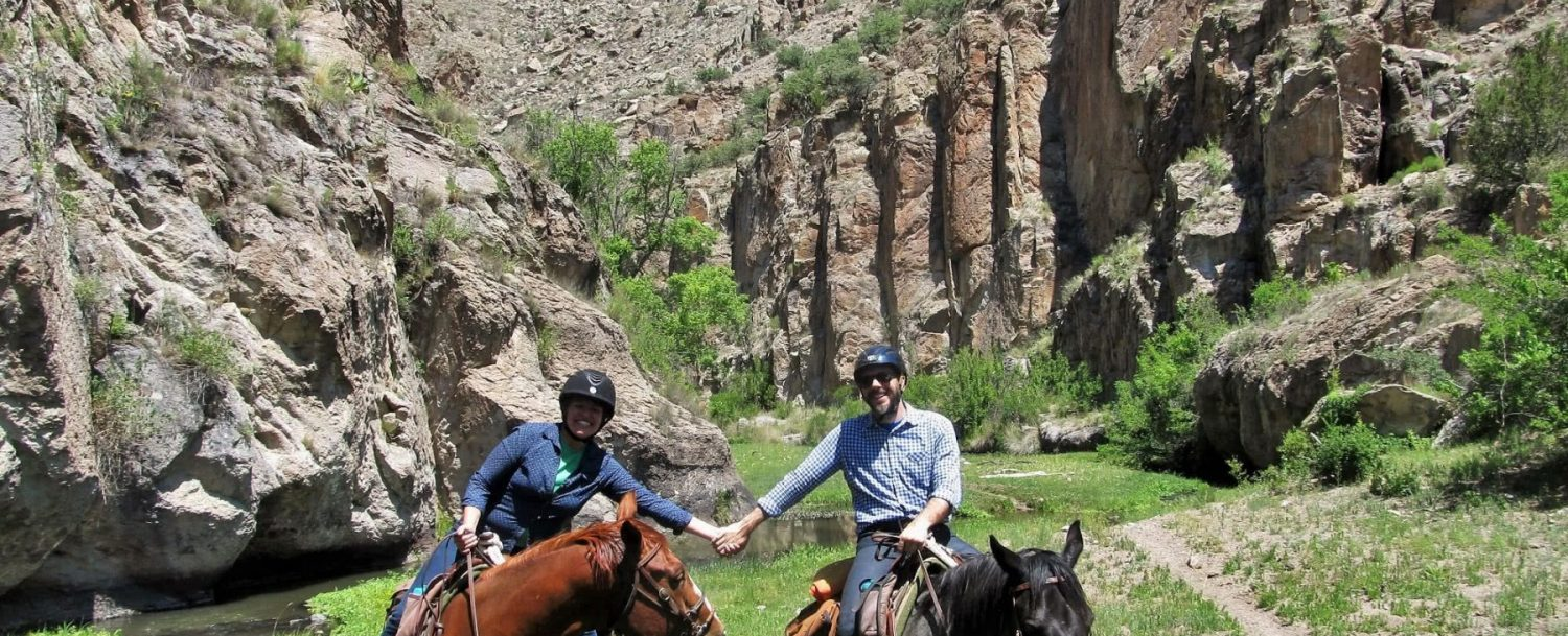 Couple on horseback: Couples and Solo Travelers at Geronimo Trail Guest Ranch.